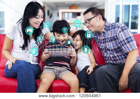 Cheerful Family With Smart Home App On Tablet
