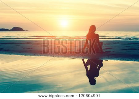 Young woman sitting on the beach, silhouette at sunset.