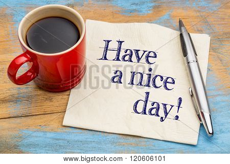 Have a nice day! Handwriting on a napkin with cup of coffee and pen