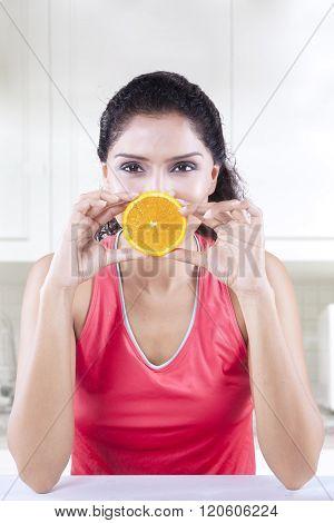 Female Model Holds Piece Of Orange Fruit