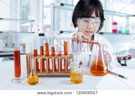 Little Girl Pouring Reagent Into Flask