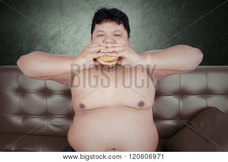 Overweight Man Enjoy Junk Food On Sofa