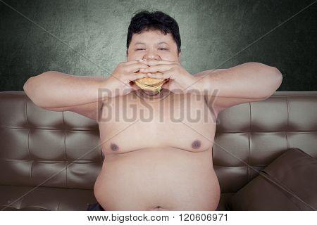 Overweight Man Enjoy Junk Food On Sofa