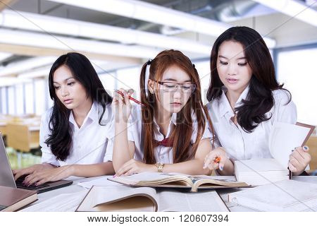 Three Beautiful Learners Studying Together In Class