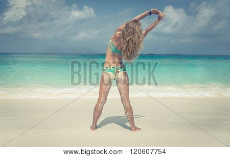 Beautiful Woman Making Yoga And Stretching On White Sand Beach