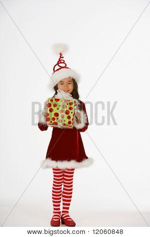 Portrait of girl dressed as elf holding gift