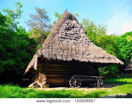 Wooden Hut With Thatched Roof In Pirogovo Museum.