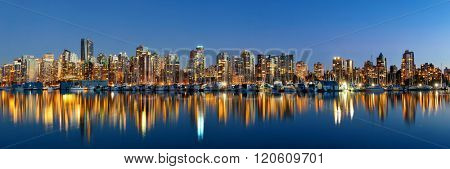 Vancouver downtown architecture and boat with water reflections at dusk panorama