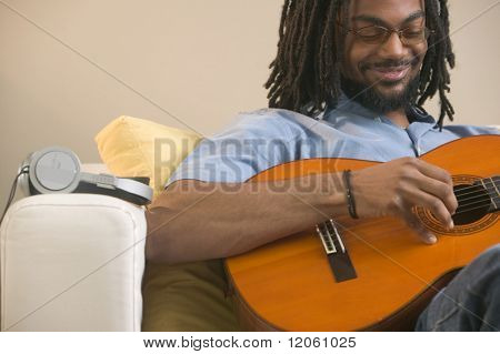 Young man sitting on a couch playing a guitar