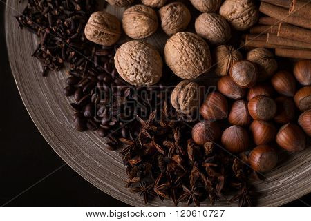 spices for baking, cinnamon sticks, star anise, cloves, nuts, coconut, coffee beans on a wooden back