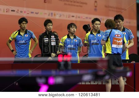 KUALA LUMPUR, MALAYSIA - MARCH 01, 2016: Kenta Matsudiara of Japan speaks with his coach and team-mates during his match in the Perfect 2016 World Team Table-tennis Championships held Malaysia.