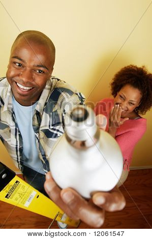 Portrait of couple changing light bulb