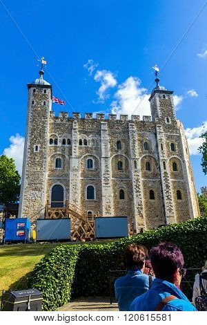 LONDON UK - JUNE 6 2015 : Unidentified tourists at Historic The White Tower in Tower of London historic castle on the north bank of the River Thames in central London - a popular tourist attraction