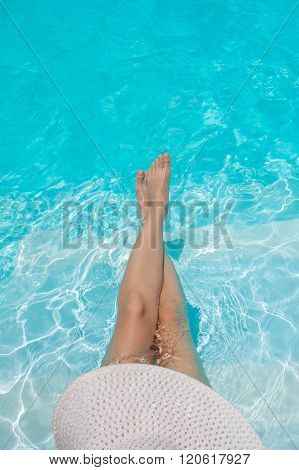 legs and a hat of woman in the pool water