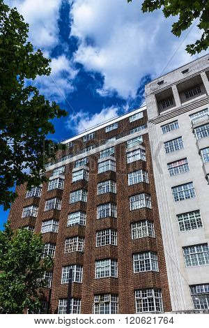 Typical English Multistory Red Brick Building  In A Summer Afternoon At Coram Street. London