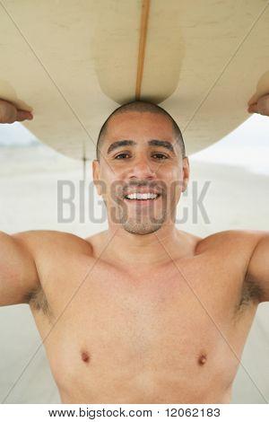 Portrait of man balancing surf board on head