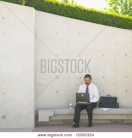 Businessman with laptop sitting on bench