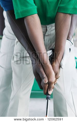 Close up of father and son's hands golfing
