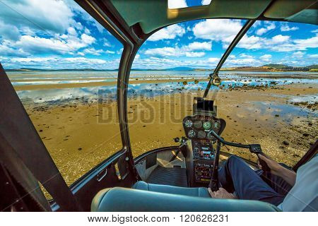 Helicopter cockpit, flying in a blue cloudy sky, with pilot arm in driving cabin. Tasman Peninsula, Australia