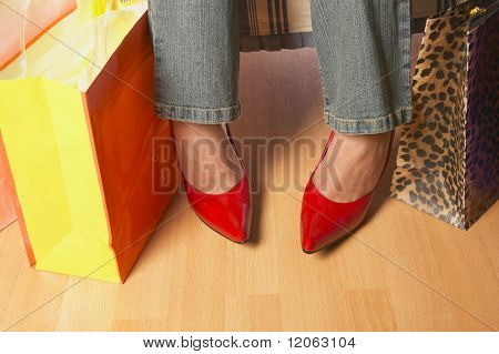 Close up of woman's feet next to shopping bags