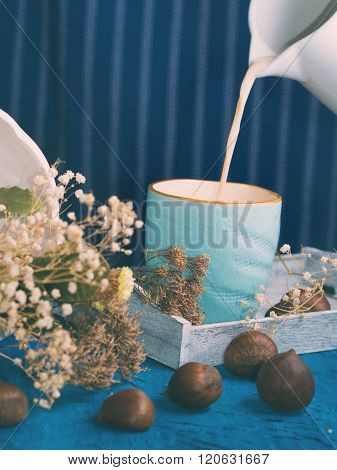 Pouring milk in a blue mug on dark blue background rustic still life. vertical shot