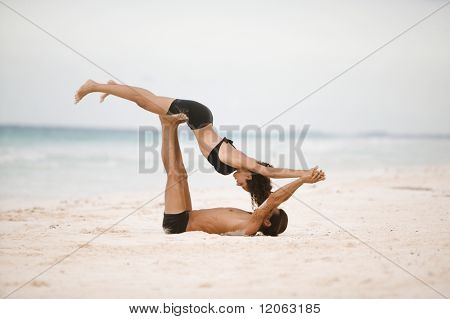 Couple practicing gymnastics on the beach