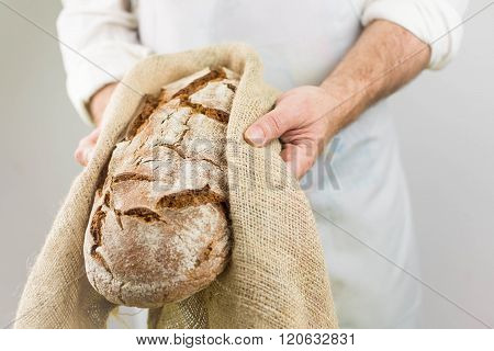 Freshly baked bread from the baker. Baker holding fresh bread in the hands.
