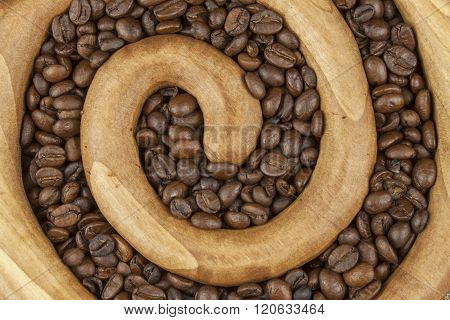 Roasted coffee beans in a wooden spiral on the canvas background. Fresh roasted coffee