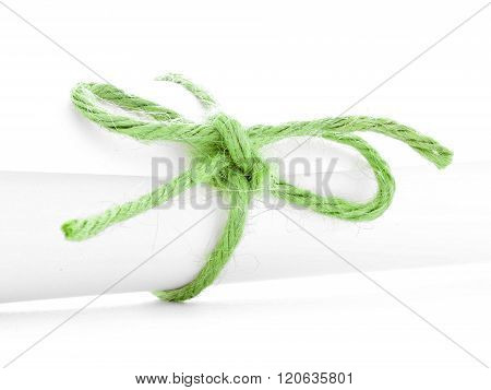 Handmade green rope node tied on white paper package isolated