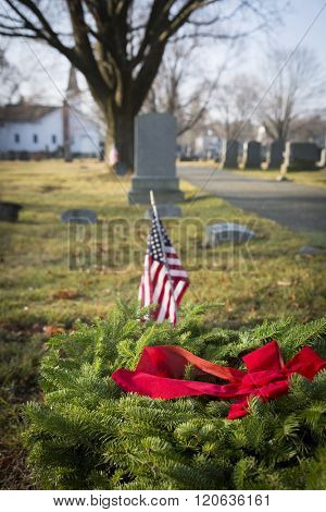 SUCCASUNNA, NJ-DEC 12, 2015: A red bow fastened to a wreath to be laid on veterans graves, with an American Flag in the background during the 2015 nationwide Wreaths Across America event.