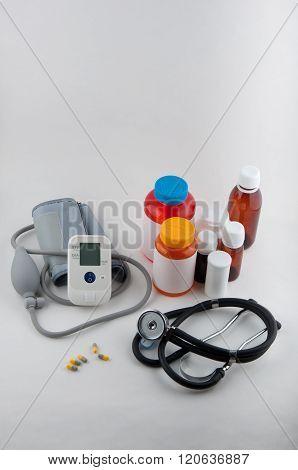 Medical Tonometer, Phonendoscope, Pills And Drug Bottles On White