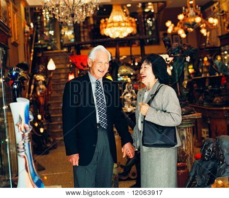 Senior couple holding hands in lighting store