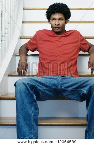 Portrait of a young man sitting on steps in a house