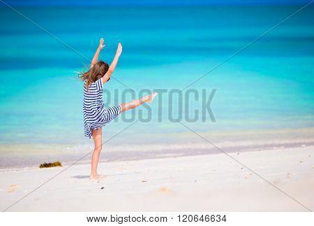 Adorable little girl having fun making cartwheel on tropical white sandy beach