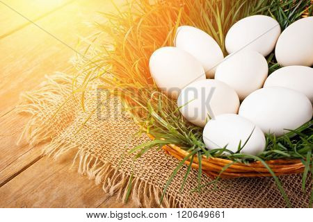 Easter eggs in brown basket with grass