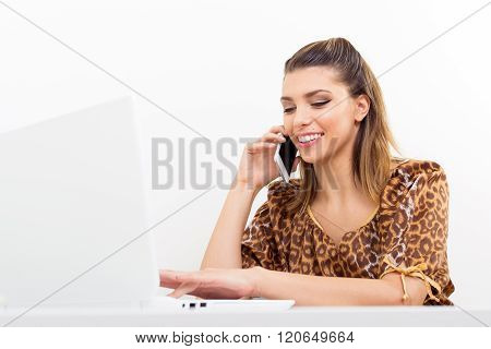 Modern young businesswoman talking on cellphone and using laptop