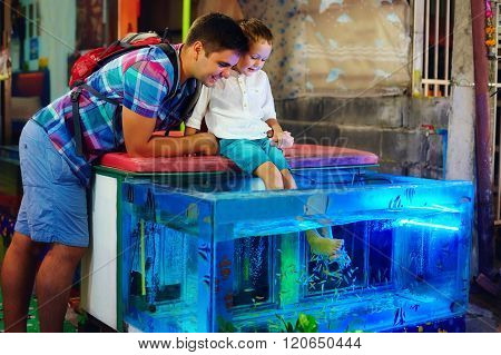 Happy Father And Son At Fish Pedicure Treatment At Street Market