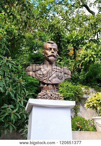 YALTA - OCTOBER 9:  Bronze bust of russian Emperor on a white pedestal on a background of green foliage -  on October 9, 2015 in Yalta