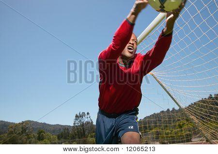 Goalie stopping ball in soccer game