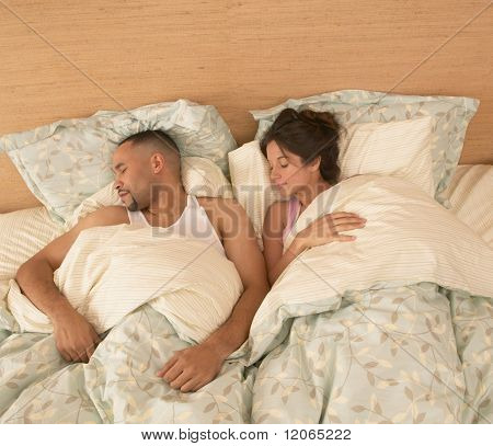 High angle view of couple asleep in bed