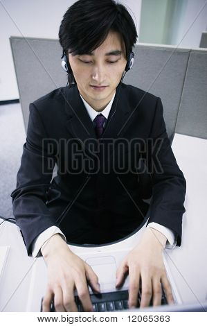Businessman sitting working on a laptop wearing headphones