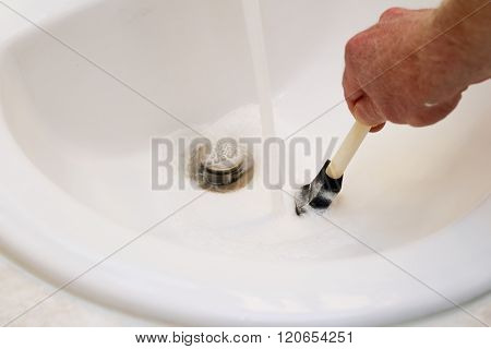 Hand Of A Man Cleaning Paint From A Paintbrush