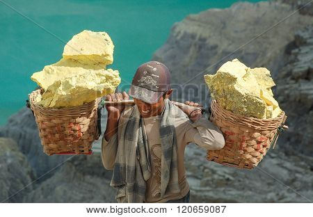 Smiling Worker Carries Sulfur Inside Kawah Ijen