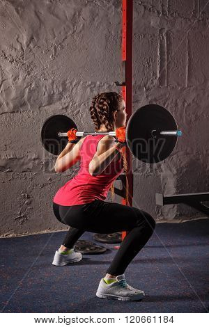 Girl Squats With A Barbell.