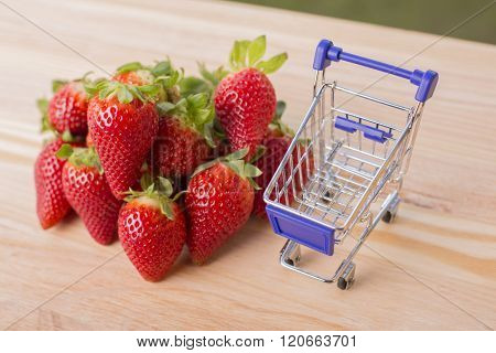 strawberries and a shopping cart on garden's table, outdoor picture