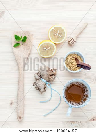 The Cup Of Ginger Tea With Ginger Roots , Ginger Powder ,lemon ,honey And Peppermint On Rustic Woode