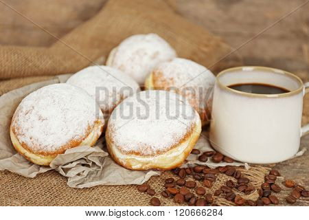 Delicious sugary donuts with coffee beans on sackcloth closeup