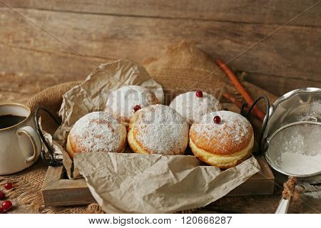 Delicious sugary donuts with red currant on tray with parchment on wooden background