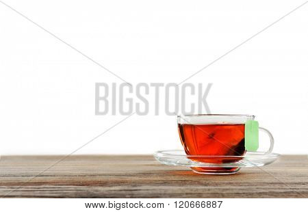 Cup of tea with tea bag on wooden background against grey background