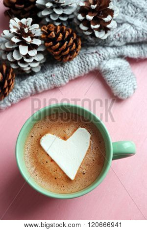 Cup of hot cappuccino with heart marshmallow, warm mittens and pine cones on pink background, close up